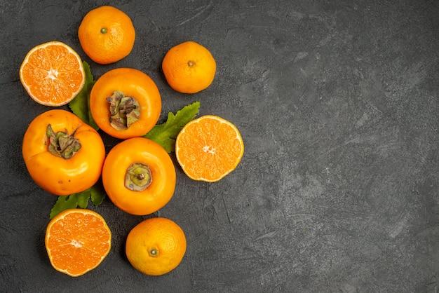 Vista dall'alto cachi freschi con mandarini su sfondo scuro