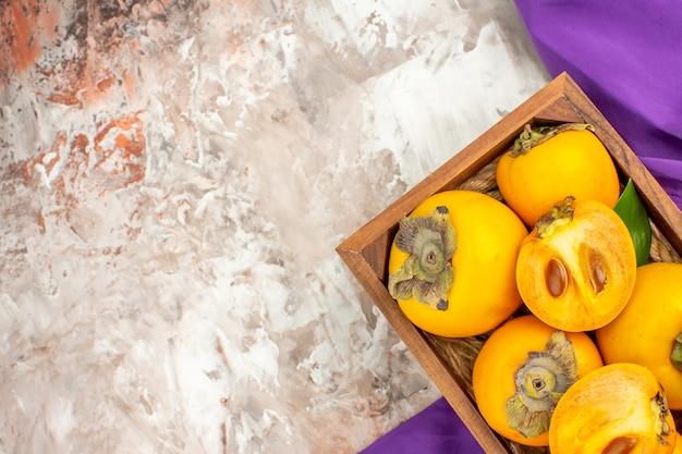 Vista dall'alto cachi freschi in una scatola di legno scialle viola su sfondo nudo