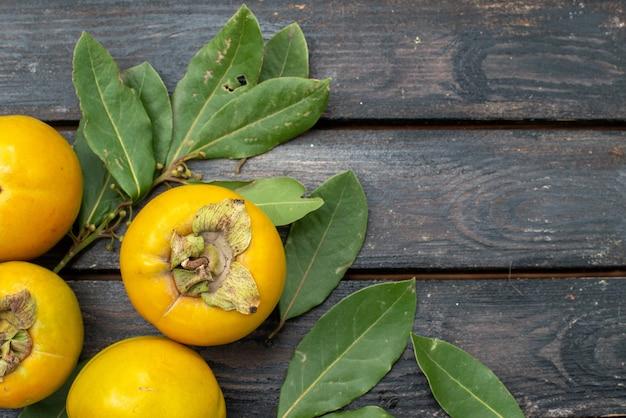 Vista dall'alto cachi freschi sulla tavola rustica in legno, frutta matura pastosa