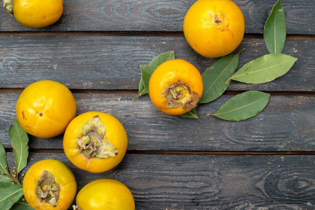 Vista dall'alto cachi freschi sulla tavola rustica in legno, frutta matura mellow