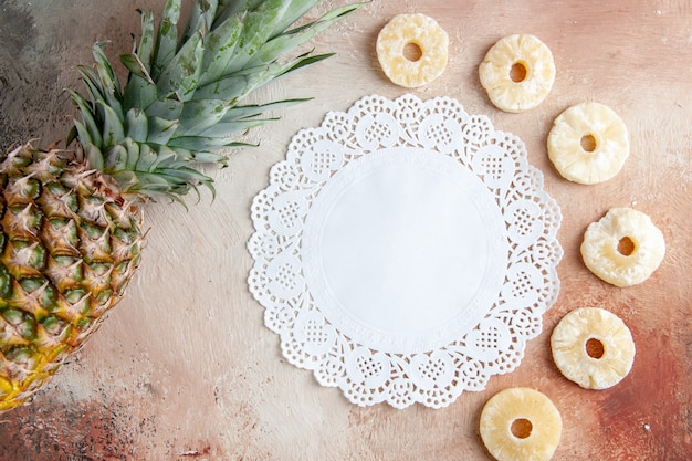Top view fresh pineapple dry pineapple rings white lace doily on beige background