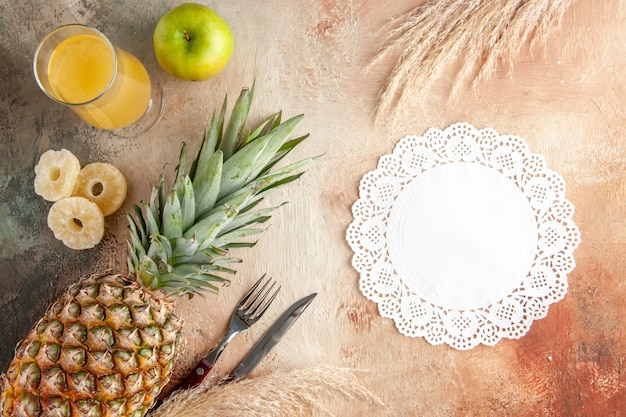 Top view fresh pineapple juice in glass apple fork and knife white lace doily on beige background