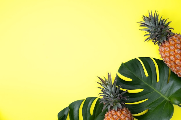 Top view of fresh pineapple with tropical palm and monstera leaves on yellow table background.