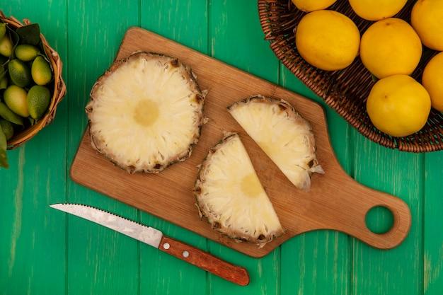 Vista dall'alto di ananas freschi su una tavola da cucina in legno con coltello con kinkans sul secchio con limoni su un secchio su una superficie di legno verde
