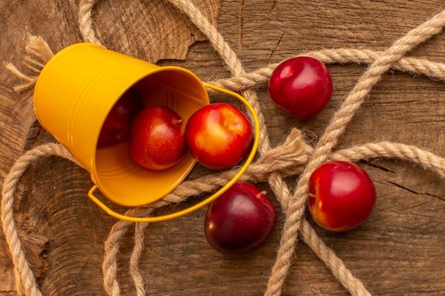 Вид сверху свежие сливы с веревками на деревянном столе, фруктовый сок, витамин, еда, спелая