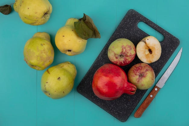 Top view of fresh pomegranate and apples on a black kitchen board with knife with quinces isolated on a blue background