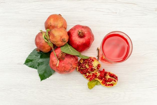 흰색 표면 주스 음료 과일 색상에 신선한 석류와 상위 뷰 신선한 석류 주스