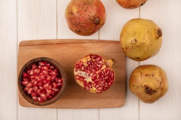 Vista dall'alto di semi di melograno freschi su una ciotola di legno su una tavola da cucina in legno con melograni isolati su una parete di legno bianca
