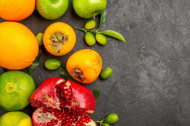 Вид сверху свежий гранат с яблоками и мандаринами на темной поверхности цвета спелых фруктов