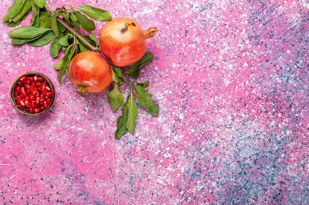 ピンクの机の上に緑の葉と新鮮なザクロの上面図