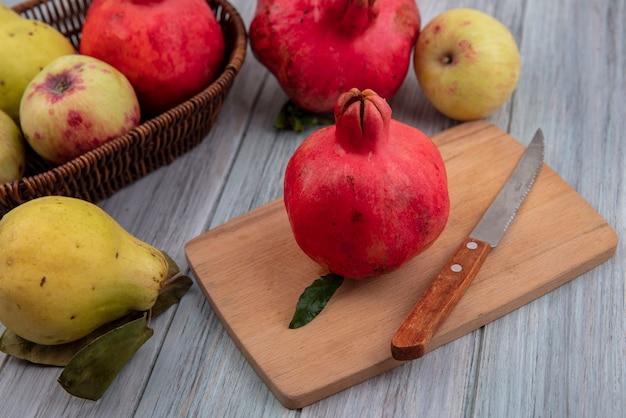 Vista dall'alto di melograno fresco su una tavola di cucina in legno con coltello con mele e mele cotogne isolato su uno sfondo grigio