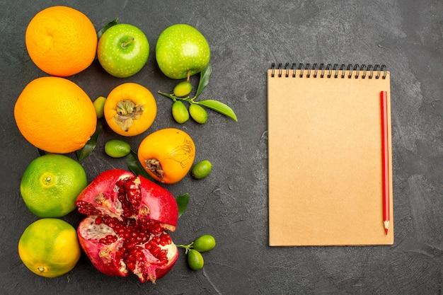 Vista dall'alto melograni freschi con mele e altri frutti sul colore della frutta matura superficie scura