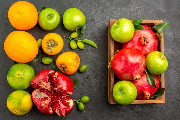 Top view fresh pomegranates with apples and other fruits on dark surface ripe fruit color