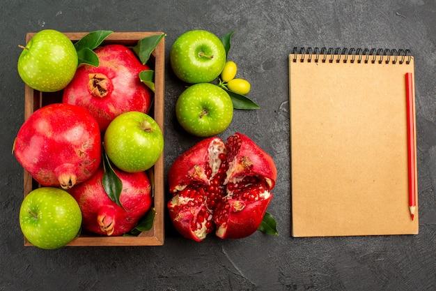 Вид сверху свежие гранаты с зелеными яблоками на темной поверхности цвета спелых фруктов