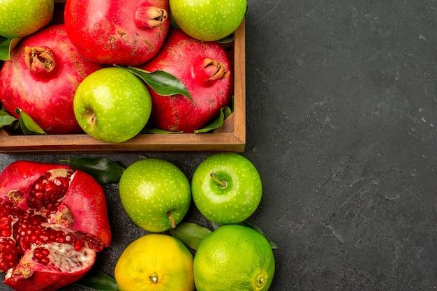 暗い表面にみかんとリンゴが付いた新鮮なザクロの上面図熟した色の果物