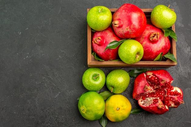 暗い表面色の熟した果物にみかんとリンゴが付いている上面図の新鮮なザクロ