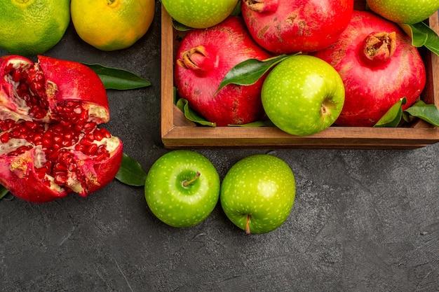 Vista dall'alto melograni freschi con mandarini e mele sui frutti maturi di colore superficie scura