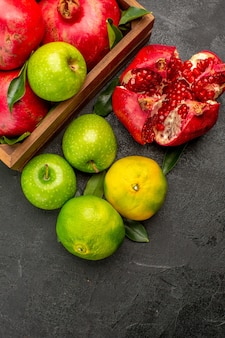 Top view fresh pomegranates with tangerines and apples on the dark surface ripe color fruit