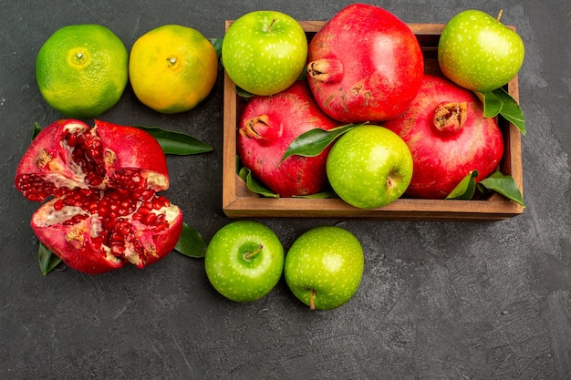 Vista dall'alto melograni freschi con mandarini e mele sul colore della frutta matura superficie scura