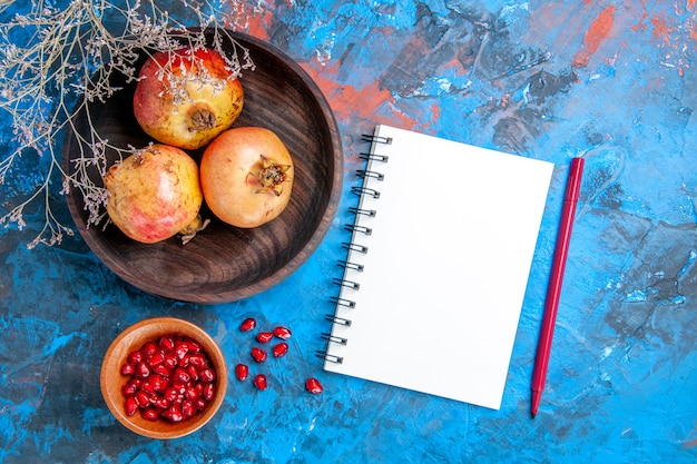 Top view fresh pomegranates in wooden bowl pomegranate seeds in a bowl a notebook red pen on blue background