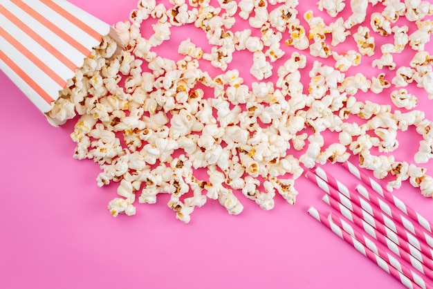 A top view fresh popcorn spread all on pink, movie corn snack