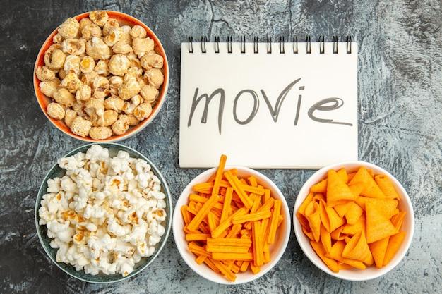 明るい表面に映画で書かれたメモ帳と軽食を備えた上面図の新鮮なポップコーン