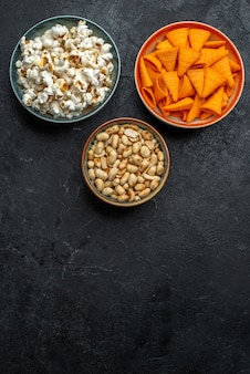 Top view fresh popcorn with nuts and chips on dark background chips snack crisp cracker