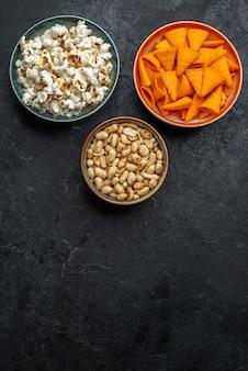 Vista dall'alto popcorn fresco con noci e patatine fritte sullo sfondo scuro patatine snack croccante cracker