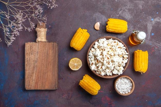 暗い表面のスナックポップコーンコーン映画工場で生の黄色いトウモロコシと油を使った新鮮なポップコーンの上面図