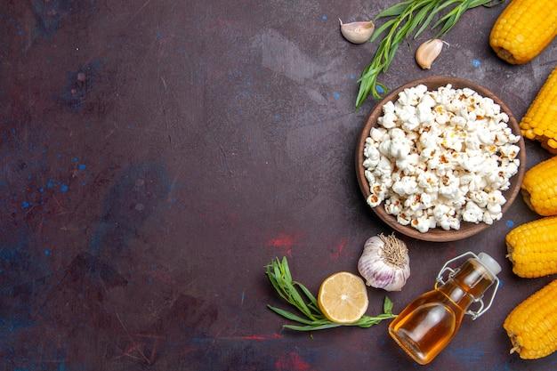 Popcorn fresco vista dall'alto con calli gialli crudi sul mais popcorn snack superficie scura