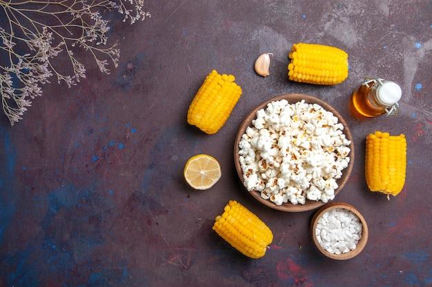 Vista dall'alto popcorn fresco con mais gialli crudi e olio sulla pianta del film di mais popcorn snack superficie scura