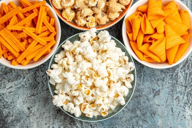 Vista dall'alto popcorn fresco con fette biscottate e patatine sulla scrivania leggera Foto Gratuite