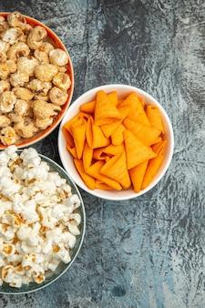 Vista dall'alto popcorn fresco con fette biscottate e patatine su una superficie chiara