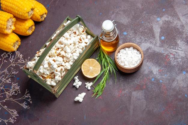 Vista dall'alto popcorn fresco con calli gialli su mais di olio di film snack superficie scura