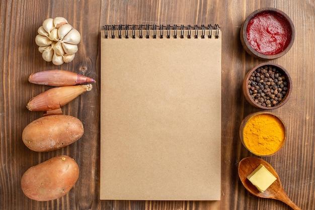 茶色の木製の机の色の生の熟した食事に調味料を入れたトップビューの新鮮なジャガイモ