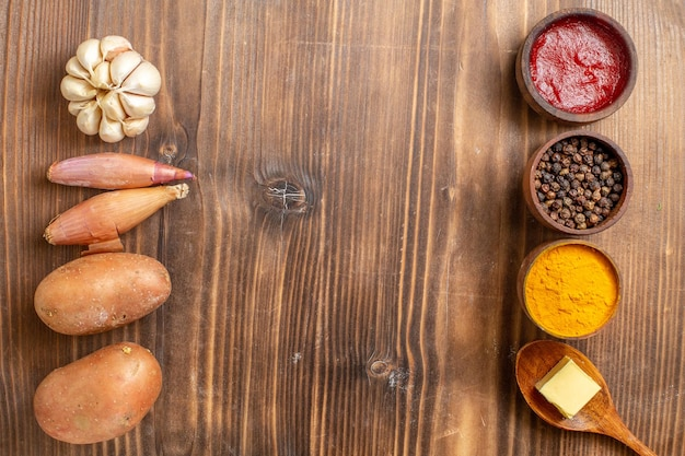 茶色の木製の机に調味料と熟した新鮮な植物の上面図新鮮なジャガイモ