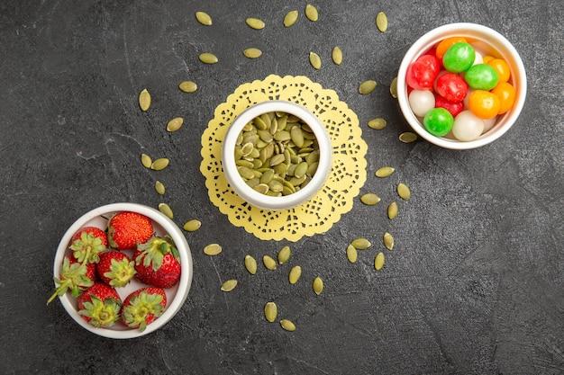 Vista dall'alto semi di zucca freschi con caramelle e fragole su sfondo grigio colore di semi di caramelle arcobaleno frutta