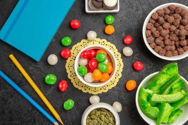ダークグレーの背景にクッキーとカラフルなキャンディーと新鮮なカボチャの種の上面図虹色の種のキャンディー