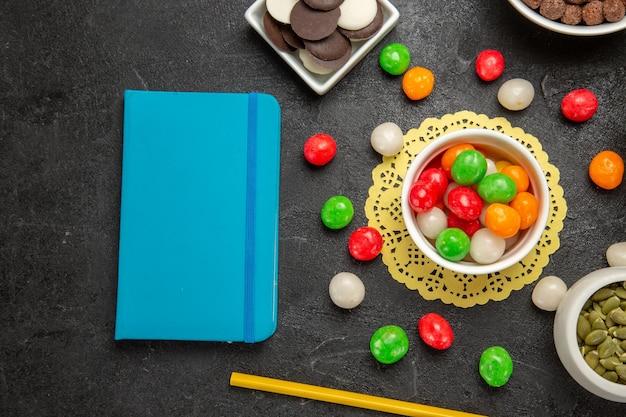 Vista dall'alto semi di zucca freschi con biscotti e caramelle colorate su sfondo grigio scuro colori arcobaleno caramelle di semi