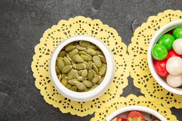 진한 회색 배경 무지개 색 씨앗 사탕에 과일과 화려한 사탕과 상위 뷰 신선한 호박 씨앗