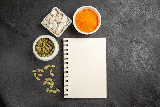 Vista dall'alto di semi di zucca freschi con zucca schiacciata e blocco note su sfondo scuro foto di semi di frutta matura oscurità