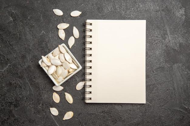 Top view fresh pumpkin seeds with notepad on dark-grey background seed fres ripe dark copybook