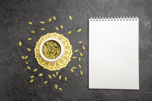 暗い背景の種子の色の多くのカボチャの顆粒にメモ帳で上面図新鮮なカボチャの種