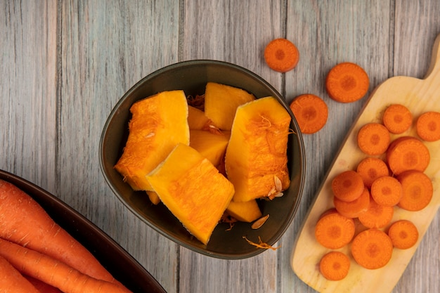 Top view of fresh pumpkin slices on a bowl with chopped carrots on a wooden kitchen board on a grey wooden wall