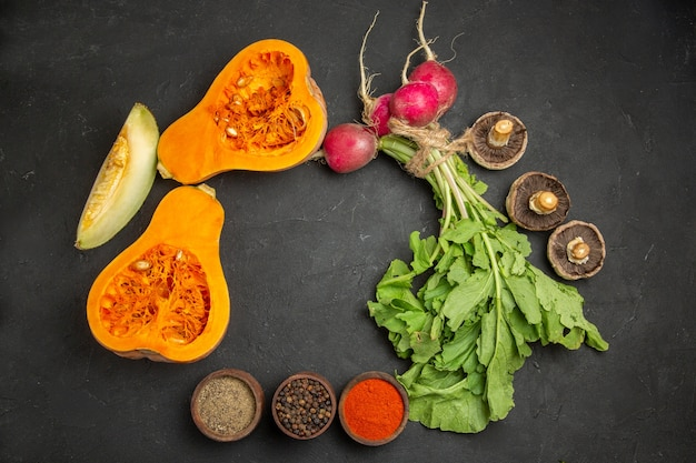Vista dall'alto di zucca fresca con verdure e ravanelli sulla scrivania scura
