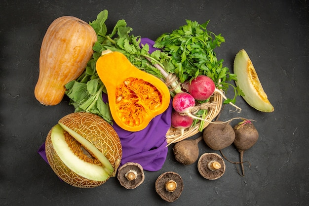 Top view of fresh pumpkin with melon radish and greens on dark background