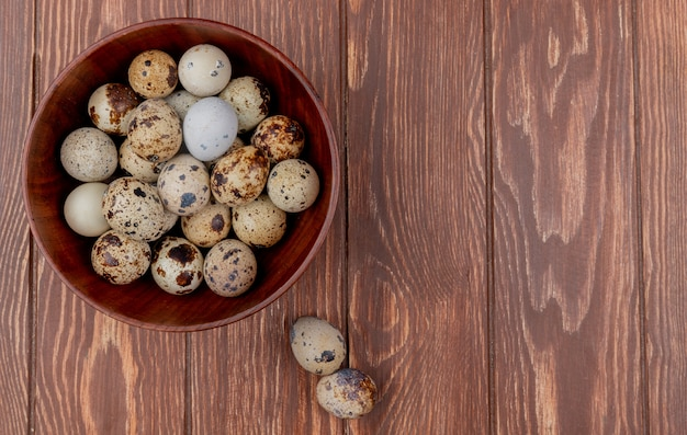 Top view of fresh quail eggs with cream colored shells on a wooden background with copy space
