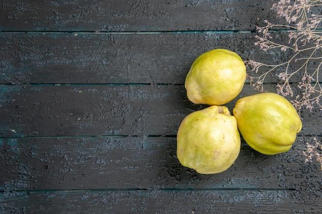 上面図新鮮なマルメロのまろやかで酸っぱい果物を紺色の机の上に植える新鮮な酸っぱい果樹が熟している