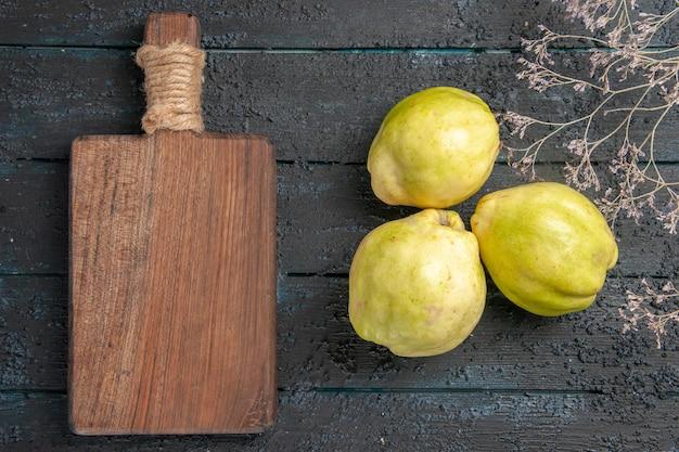 Вид сверху свежей айвы, спелых и кислых фруктов на темно-синем столе, спелых свежих кислых фруктовых деревьев
