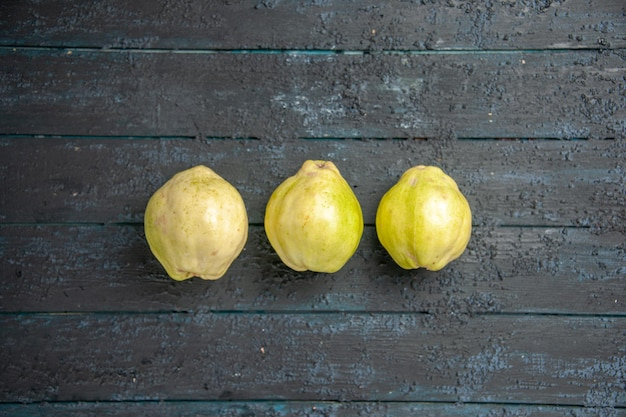 Top view fresh quinces mellow and sour fruits on dark-blue desk ripe fetus fresh tree sour plant